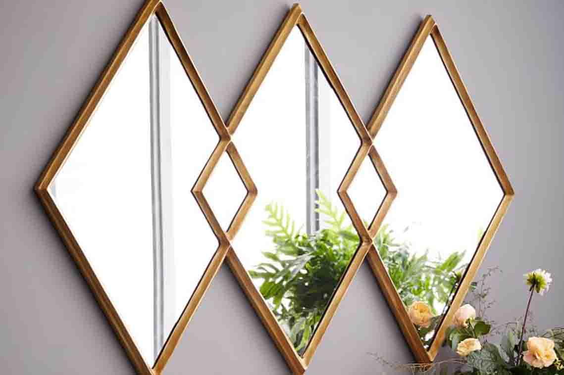 Stylish diamond shaped three joint mirror on purple wall