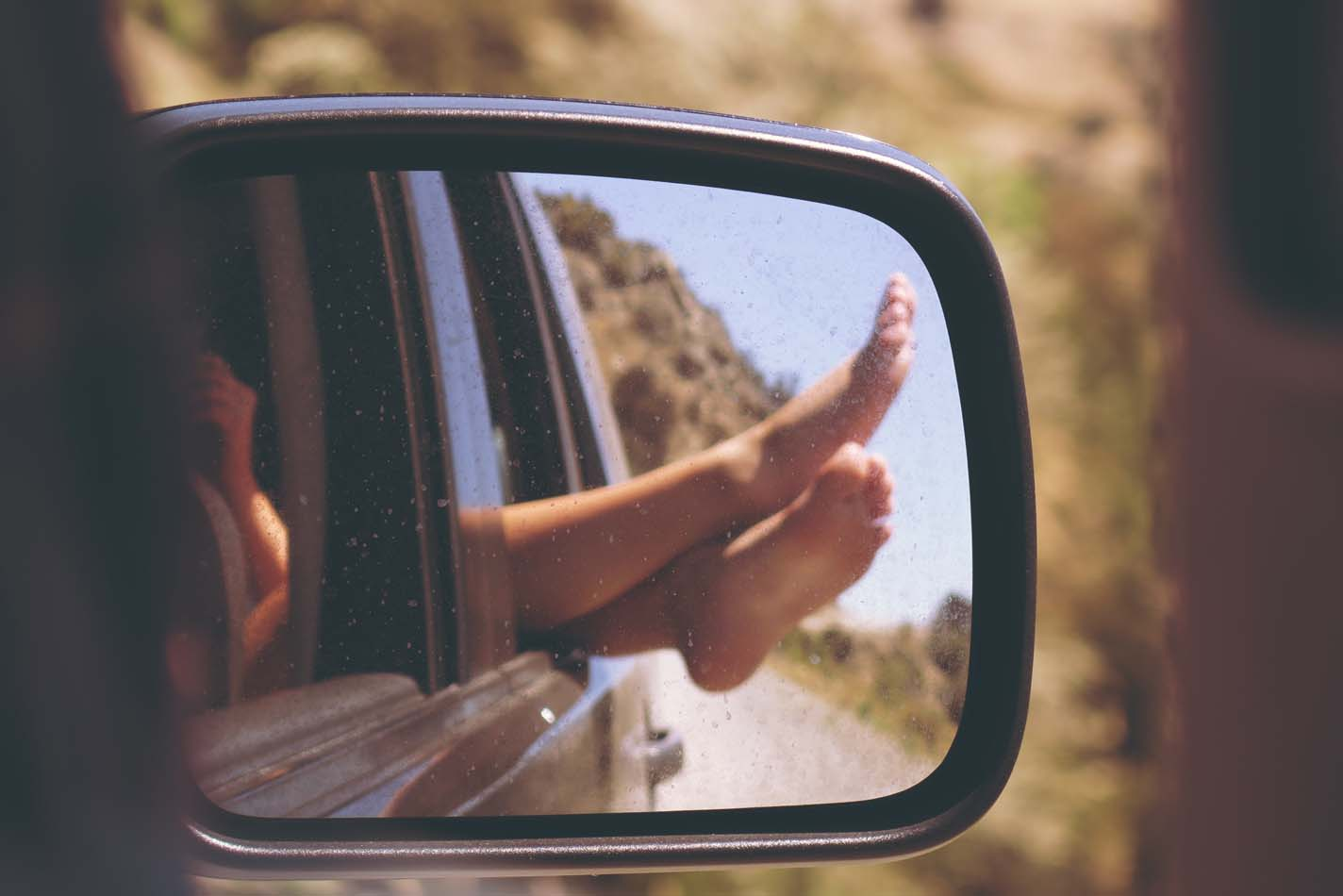 Woman legs outside car window captured through side view mirror