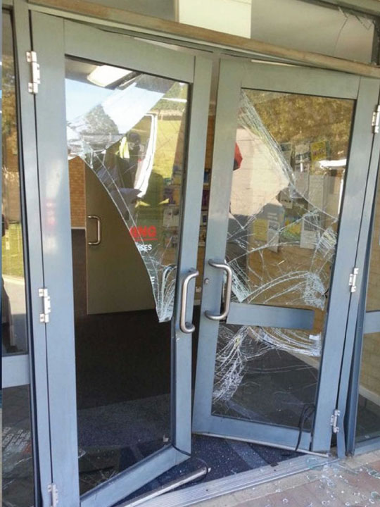 Smashed glass on a front door for a building